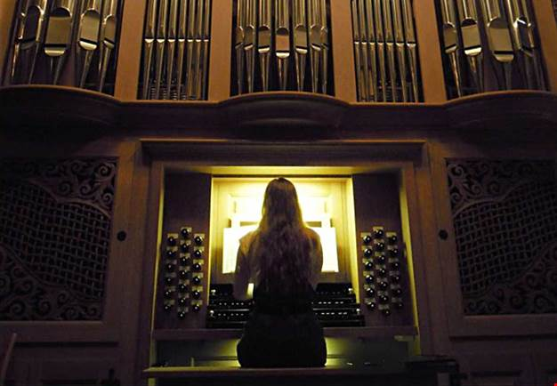 Woman with long hair sitting with her back to the camera. Playing on a magnificent organ. Photography.