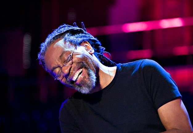 Man with rastafari hair playing piano. Photography.