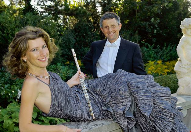 Woman with a flute and a man in dark suit. Photo.. Fotografi.