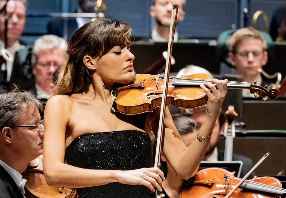 Woman in concert dress playing with empathy on her violin