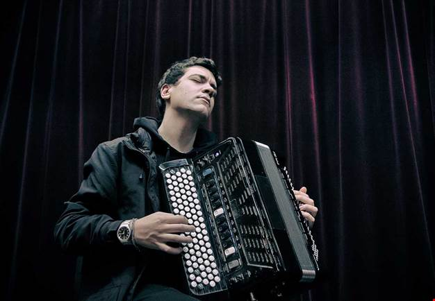 Man with black jacket holding his accordion in his hand. Photography