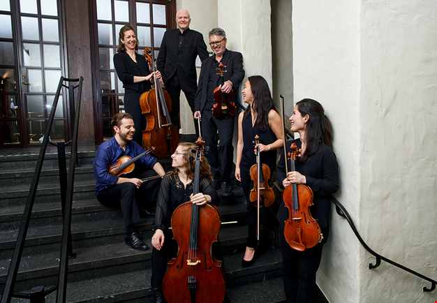 Picture of the whole ensemble standing together in a staircase.