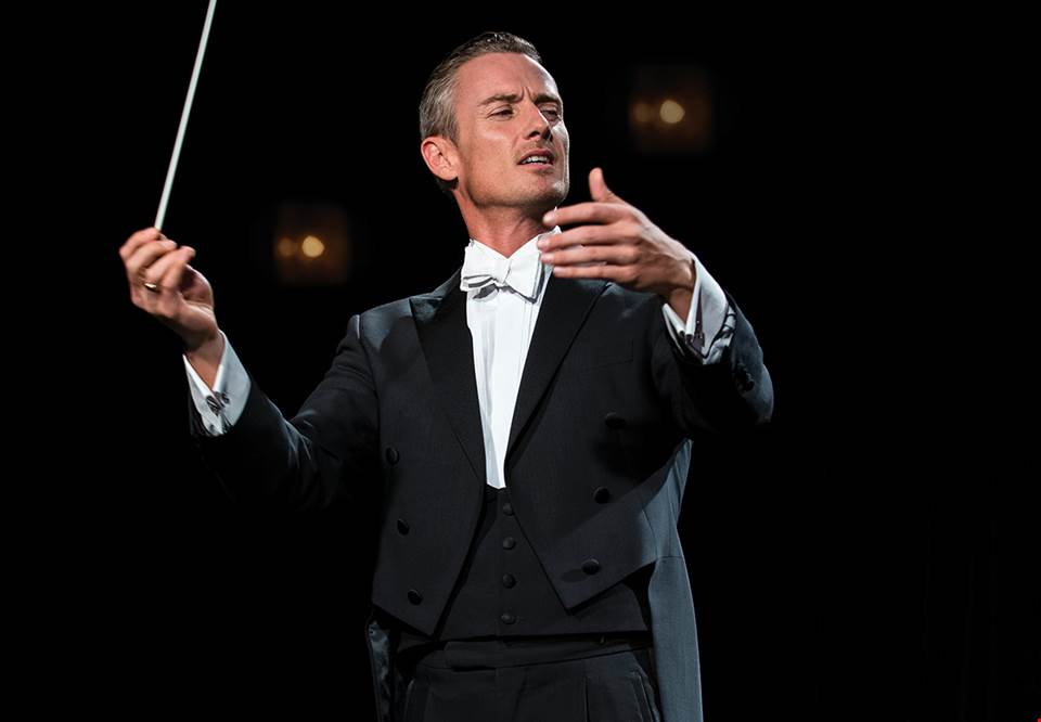 Man conducting on stage. Photo.