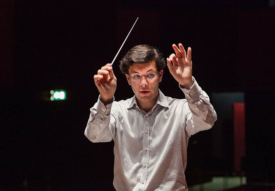 Man with white shirt conducting. Photo.