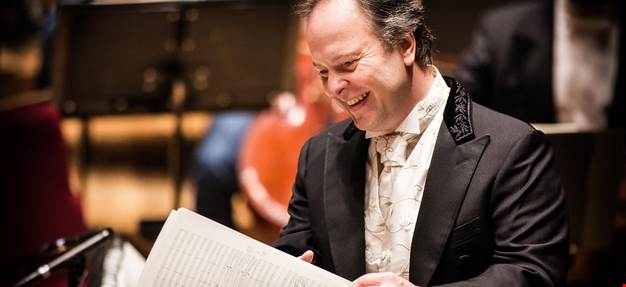 The conductor going through a score with a happy smile on his face.