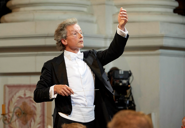 Franz conducts vividly. Dressed for concert. Photography.