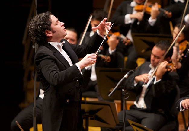 Gustavo Dudamel conducting on stage surrounded by musicans. Photo.