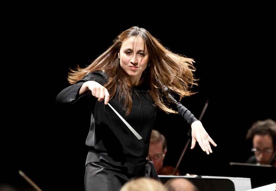 Women with dark long hair conducting on stage. Photo.