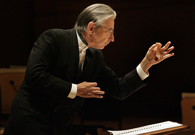 Conductor Michael Tilson Thomas in concert, focused and with his left hand making a pointillistic sign. Photography.
