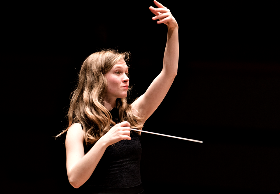 Young woman conducting. Photo.