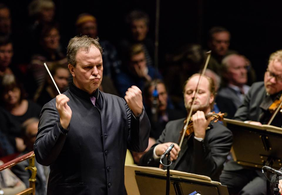 Intense moment of Sakari Oramo conducting the Royal Stockholm Philharmonic Orchestra, both hands raised and a grim expression on his face. Photography.