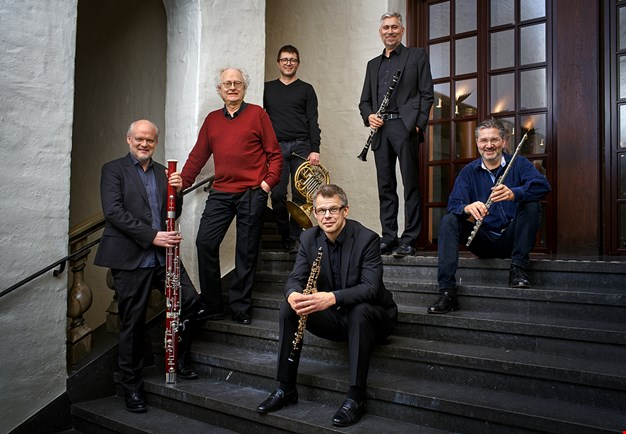 Six men sitting in stairs with their instruments. Photo.