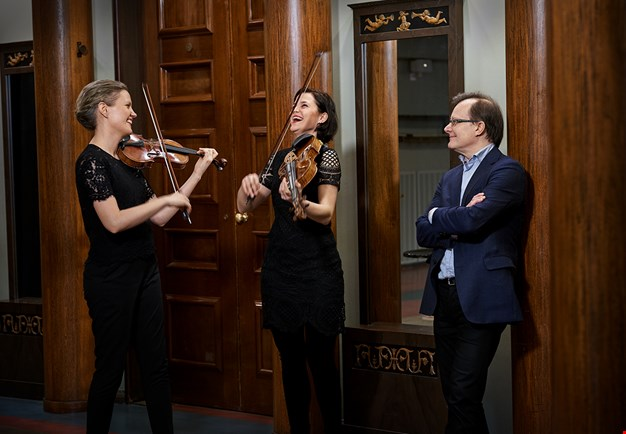 Two women laugihng with their violins and one man standing leaning againt a pilar. Photo.