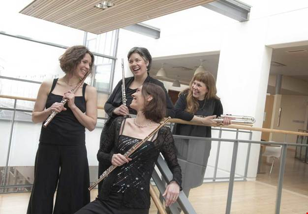 Three women, dressed for concert, with their flutes in their hands. Photo.