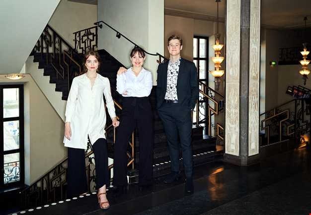 Three persons standing in a corridor