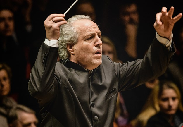 Conductor on stage in front of large orchestra