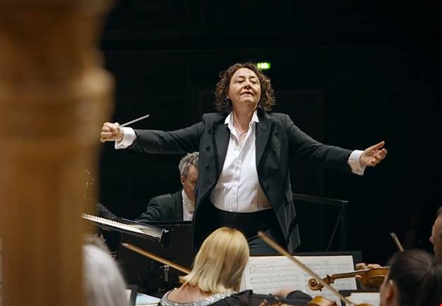 Female conductor conducting large orchestra. Photo.