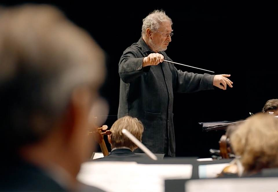 Conductor on stage in front of the large orchestra. Photo.