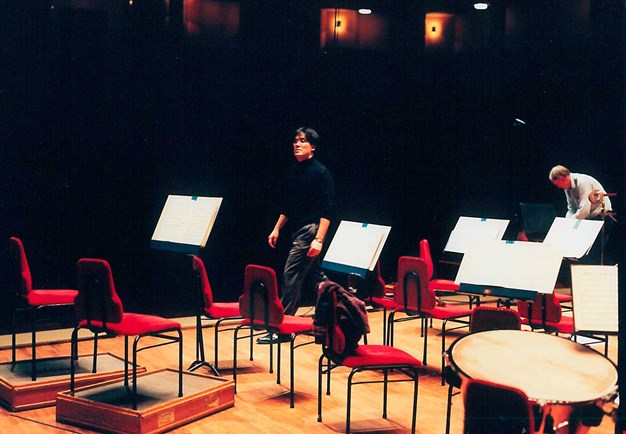 The conductor walking off the stage after a rehearsal, empty seats around him on the podium. Photograph.