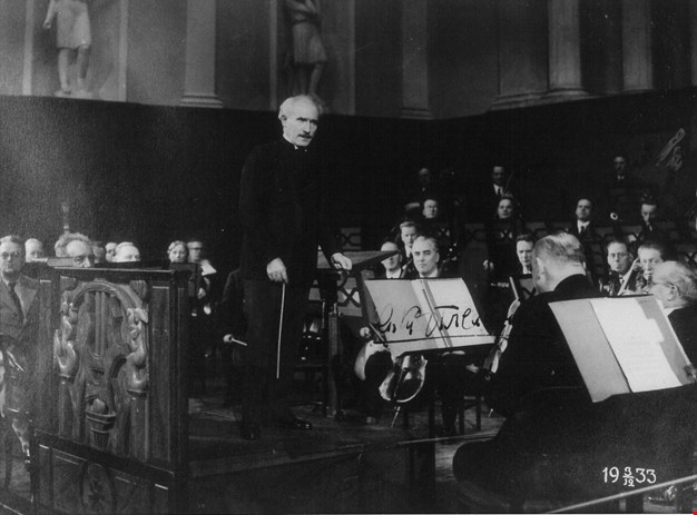 The conductor talking to the orchestra during rehearsal. Black and white photograph.
