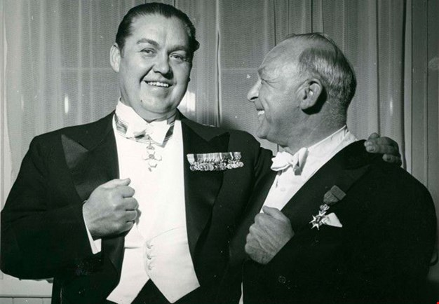The singer and the conductor laughing together in a dressing-room at Konserthuset. Black and white photograph.