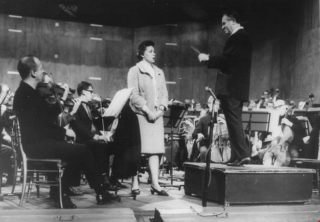 Black and white photo of the orchestra and singer rehearsing.