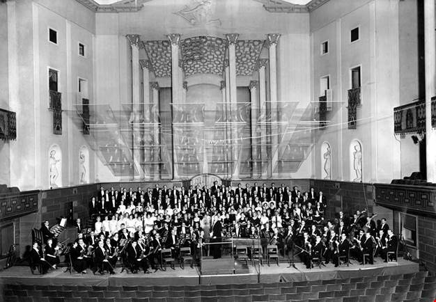 Black and white photo of the conductor and the orchestra posing in the main hall of Konserthuset.