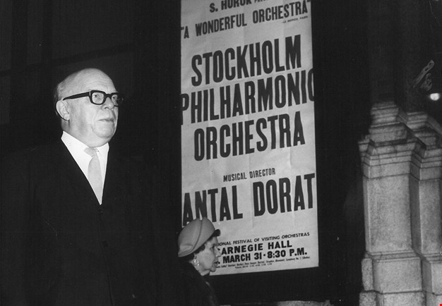Black and white photograph of the director standing, posters of the orchestra's concert are clearly visible in the background.