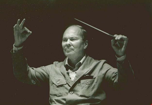Close-up of the conductor in rehearsal. Black and white photograph.