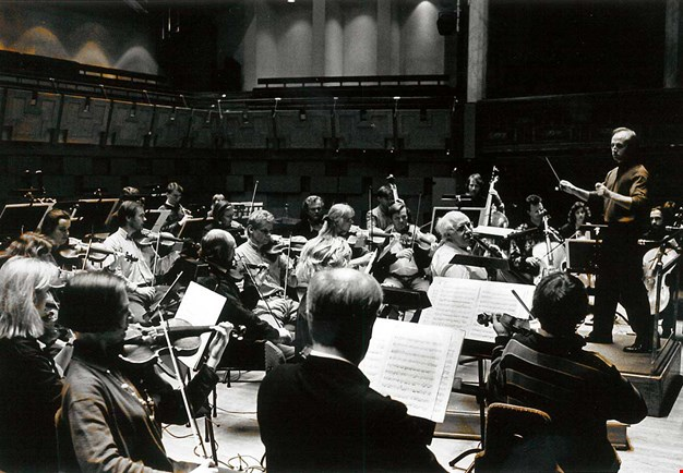 Black and white photograph from a rehearsal in the main hall, the conductor is viewed from the side as well as large parts of the musicians.