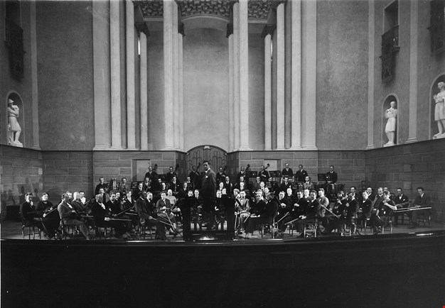 Black and white photograph of the orchestra and its conductor, from the main hall at Konserthuset.