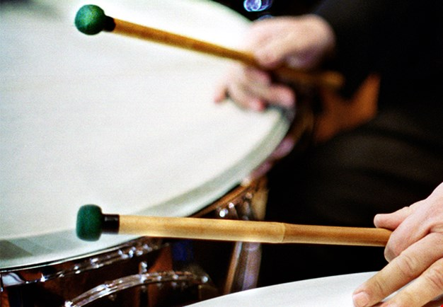Close up of timpanist playing, showing hands holding the sticks above the timpani. Photography.
