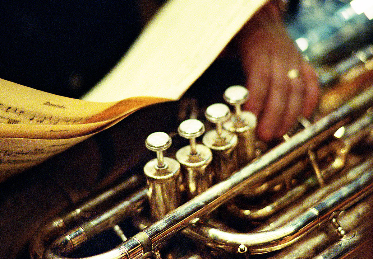 Close-up of a brass instrument and some pages of sheet music. Photography.