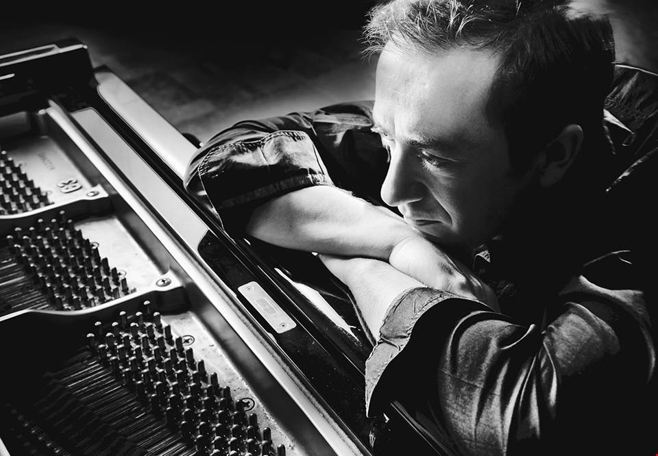 Man who is leaning against a piano. Photo. Fotografi.