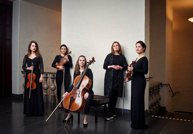 Five women standing with their instruments. Photo.
