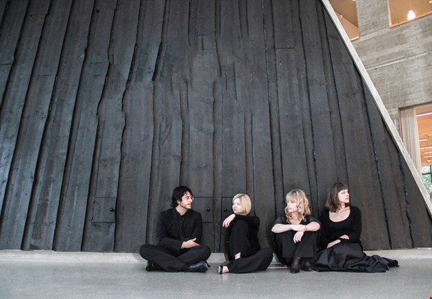 The quartet sitting talking to each other on the floor in front of a black wooden wall. Photography.