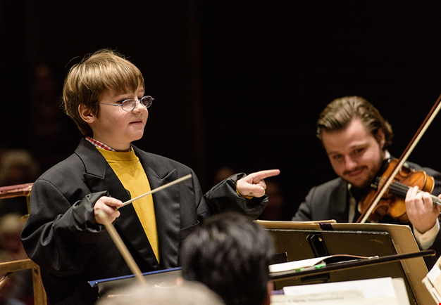 Litte kid conducting the orchestra