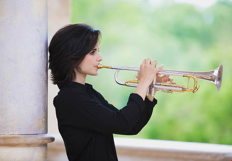 Young woman with dark hair playing trumpet. Photo.