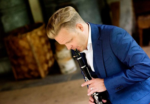 Christoffer plays his clarinett. Picture taken in profil. Photo.