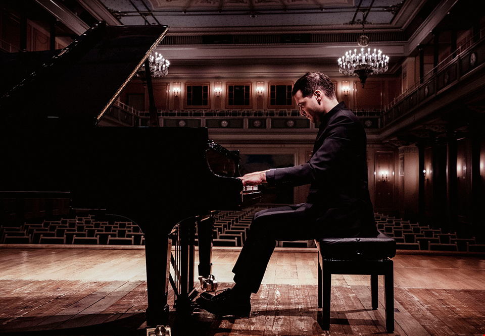 Francesco is playing on his piano at a concerthall. Photo.