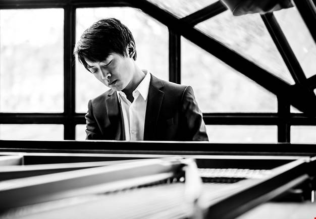 Young guy by a piano. Black and white photo.