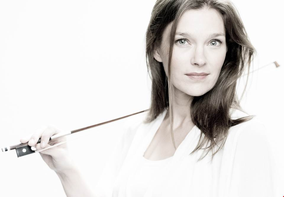 Violinist Janine Jansen looking into the camera with the bow resting on her right shoulder. Photography.