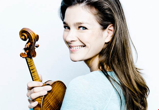 Woman holding a violin, smiling towards the camera. Photo.