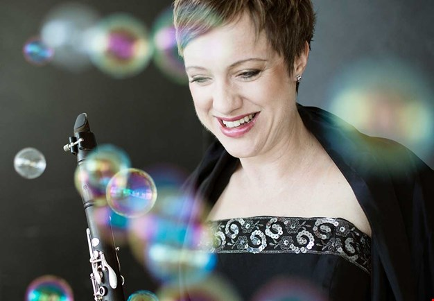 Close up of the musician holding her clarinet and looking downwards. Photo.