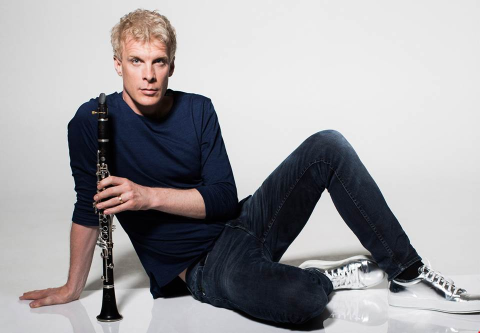 Martin Fröst sitting on a white floor in front of a white background, holding the clarinet standing up on the floor in front of him.
