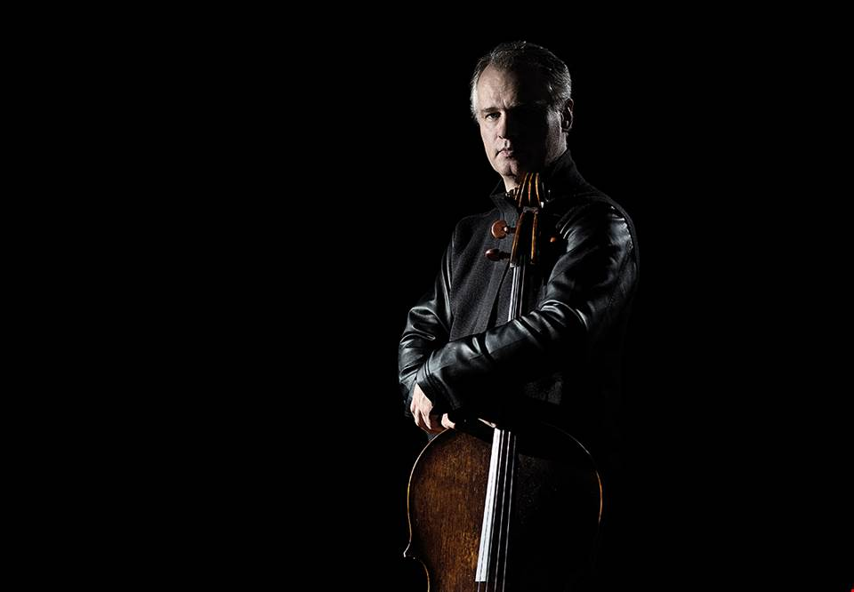 Cellist Torleif Thedéen standing up in sparse lighting, holding the cello beside him and looking at the camera with half his face in shadows. Photography.