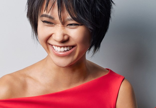 Close-up of the pianist Yuja Wang dressed in red, smiling and slightly frowning her nose. Photography.